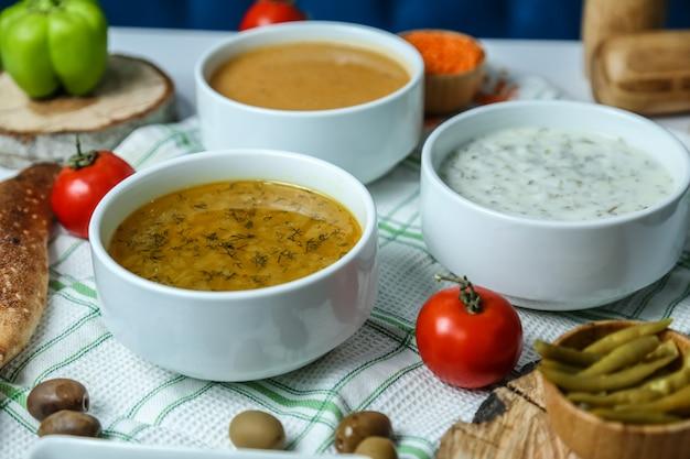 Sopa de galinha vista frontal com sopa de lentilha e iogurte com tomate e azeitonas em cima da mesa