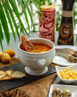 Sopa de lagostins com torradas e calos no quadro negro na toalha de mesa de serapilheira