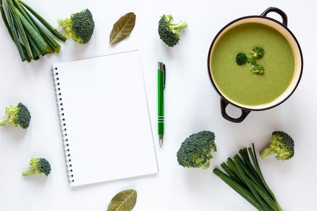 Sopa de legumes brócolis com o bloco de notas vazio