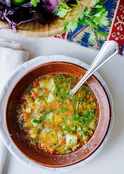 Sopa de legumes com ervas dentro da tigela marrom.