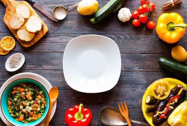 Sopa de legumes fresca, feita em casa, na mesa rústica de madeira, vista superior