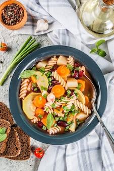 Sopa de legumes italiana minestrone com macarrão fusilli, conceito de comida vegetariana