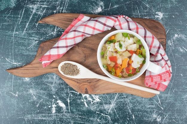 Sopa de legumes na placa de madeira com colher e toalha de mesa.