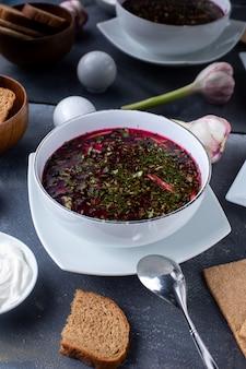 Sopa de legumes vermelho borsh com pão e creme de leite na mesa cinza