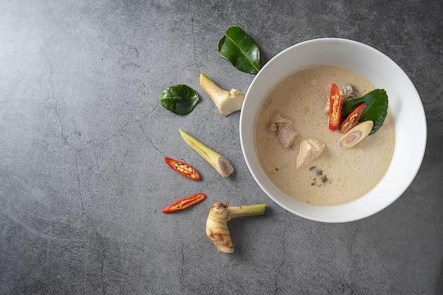 Sopa de leite de coco com frango (tom kha gai) em fundo escuro, comida local tailandesa