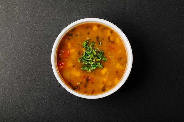Sopa de lentilha com ingredientes misturados e ervas em uma tigela branca.