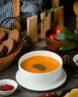 Sopa de lentilha em uma tigela branca e uma cesta de pão
