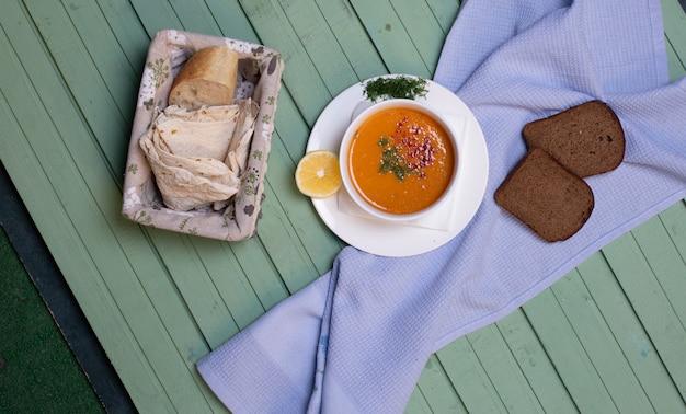 Sopa de lentilha servida com fatias de limão e pão em uma mesa azul