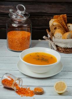 Sopa de lentilha servida com fatias de limão e pão