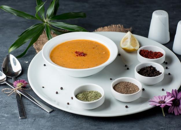 Sopa de lentilha servida com limão, sumagre, bolinhas de pimenta preta e hortelã seca