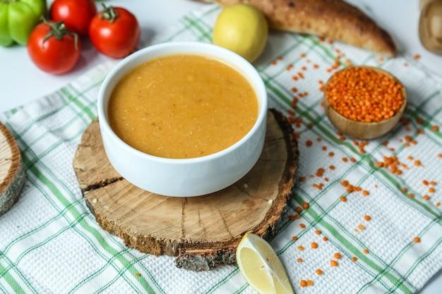 Sopa de lentilha turca tradicional vista lateral com tomate e limão em cima da mesa