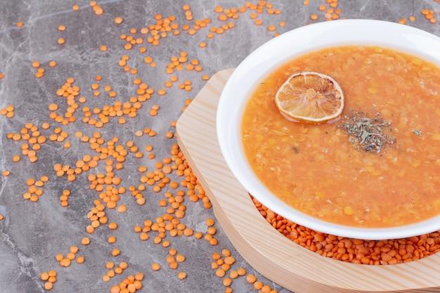 Sopa de lentilha vermelha com uma rodela de limão e especiarias.