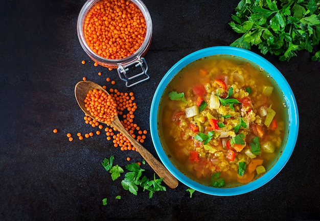 Sopa de lentilha vermelha no fundo escuro. conceito de alimentação saudável. comida vegana.