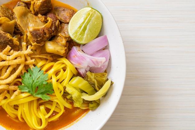 Sopa de macarrão ao curry do norte da tailândia com carne de porco refogada - comida tailandesa