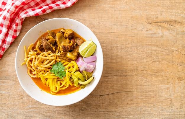 Sopa de macarrão ao curry do norte da tailândia com carne de porco refogada - estilo tailandês