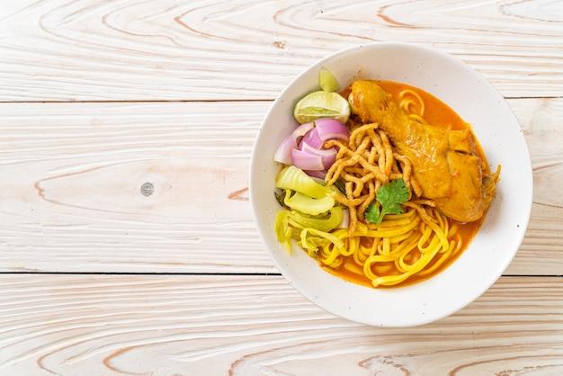 Sopa de macarrão ao curry do norte da tailândia com frango (kao soi kai) - comida tailandesa