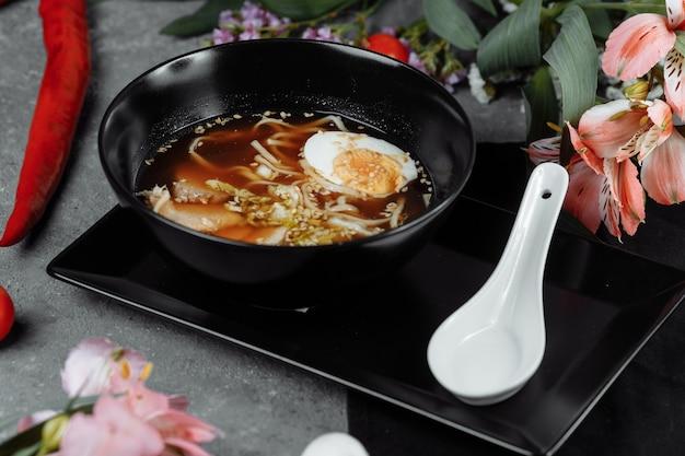 Sopa de macarrão asiática, ramen com frango, tofu, legumes e ovo em uma tigela preta.