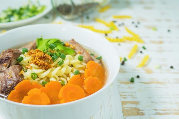 Sopa de macarrão com carne de porco e cenoura na mesa de madeira branca