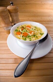 Sopa de macarrão com cenoura na mesa de madeira