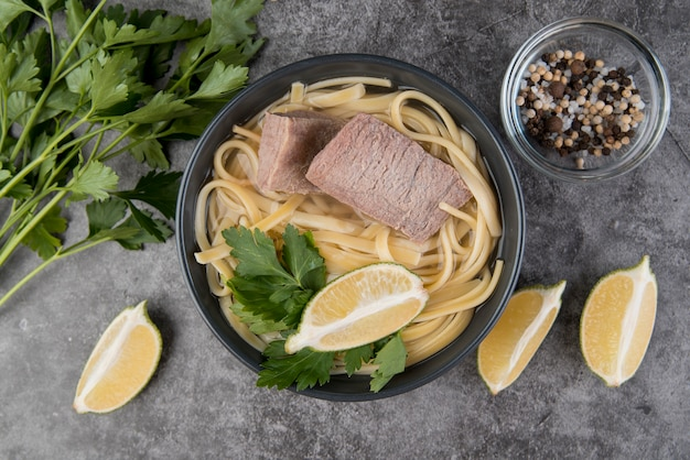 Sopa de macarrão com fatias de limão e salsa