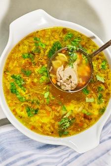 Sopa de macarrão com frango em uma panela com concha de sopa, vista de cima