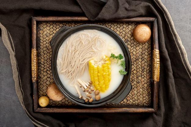 Sopa de macarrão com milho em uma tigela preta em uma mesa de madeira