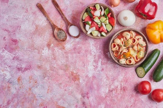 Sopa de macarrão com molho de tomate em um copo de madeira servido com salada de legumes.
