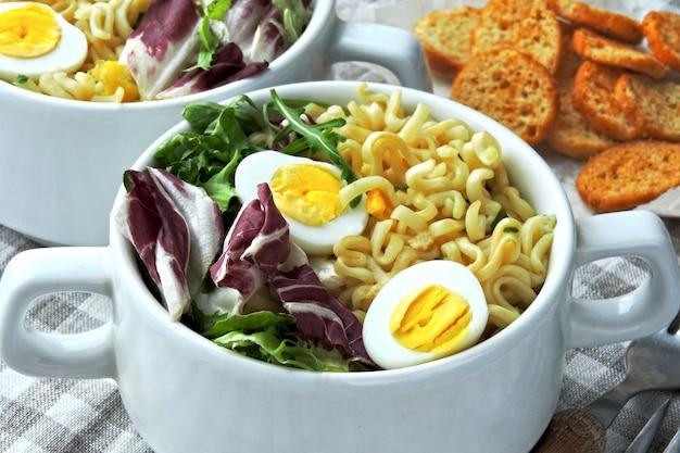 Sopa de macarrão com ovos de codorna e salada mix
