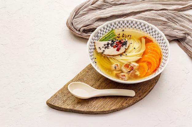 Sopa de macarrão coreano com frango defumado e legumes. prato picante para refeição saudável