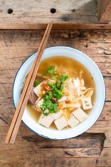 Sopa de macarrão de arroz vietnamita com carne de porco e frango na mesa de madeira