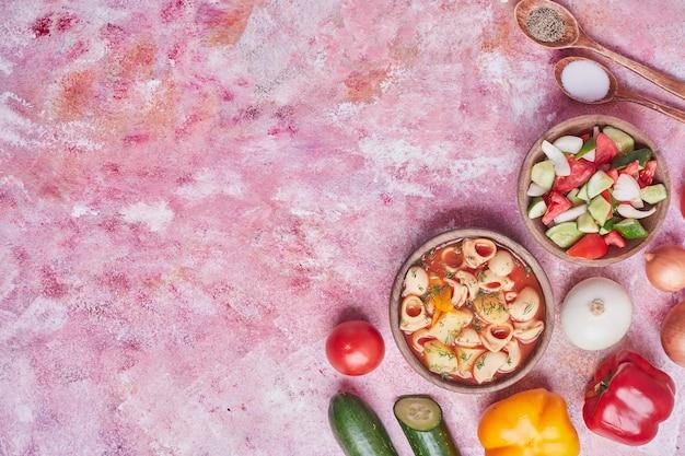 Sopa de macarrão em molho de tomate com salada de legumes.