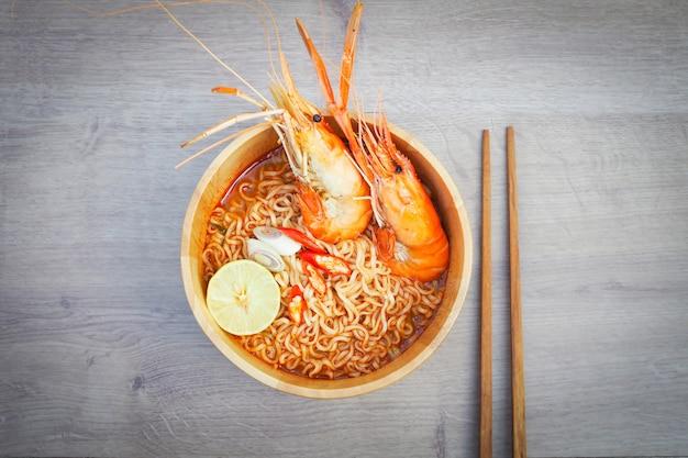 Sopa de macarrão instantâneo picante com camarão na tigela de madeira no fundo de madeira