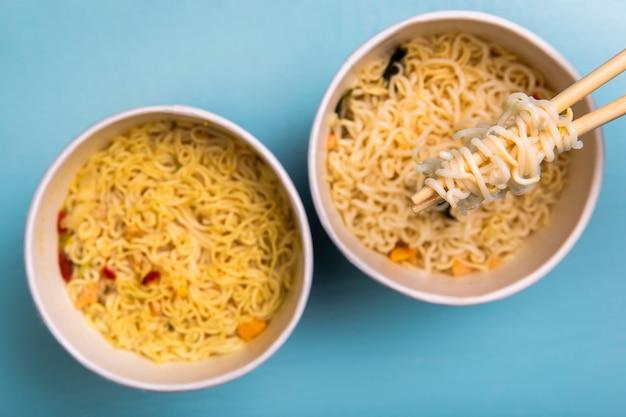 Sopa de macarrão ramen plana leigos em tigelas com pauzinhos