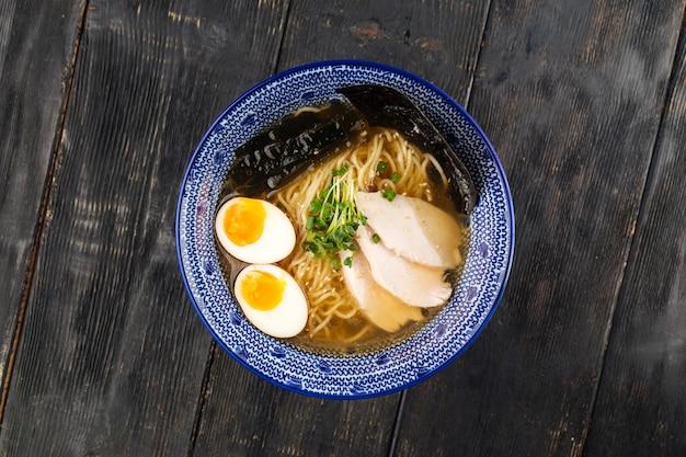 Sopa de macarrão shio ramen japonês com peito de frango na mesa de madeira