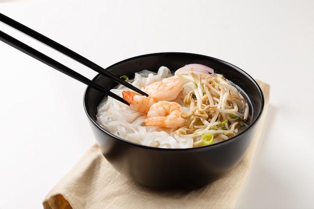 Sopa de macarrão vietnamita tradicional pho com camarões na tigela preta