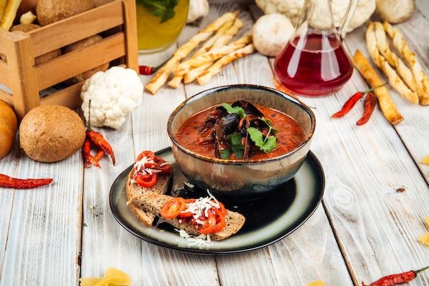 Sopa de mexilhões de tomate com manjericão de cebola e torradas
