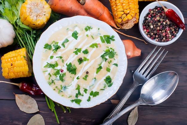 Sopa de milho em uma placa de cerâmica e ingredientes