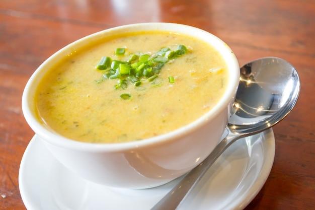 Sopa de milho em uma tigela branca na mesa de madeira