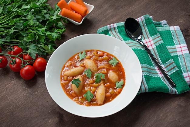 Sopa de minestrone com macarrão e ervas. cozinha italiana. fundo de madeira branco.
