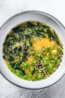 Sopa de miso japonesa em uma tigela branca. fundo branco. vista do topo