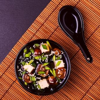 Sopa de miso japonesa em uma tigela preta no guardanapo de bambu.