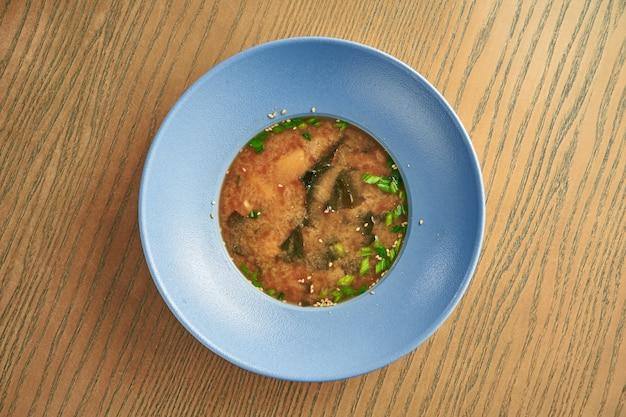 Sopa de miso japonesa tradicional em uma tigela azul em uma parede de madeira. comida saudável e dietética. fechar-se