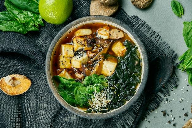 Sopa de miso vegetariana fresca com cogumelos shiitake, queijo tofu e algas em um pano cinza. comida saudável e equilibrada. vista do topo.