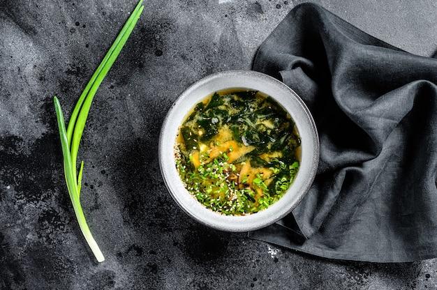Sopa de missô com tofu e algas marinhas. fundo preto. vista do topo