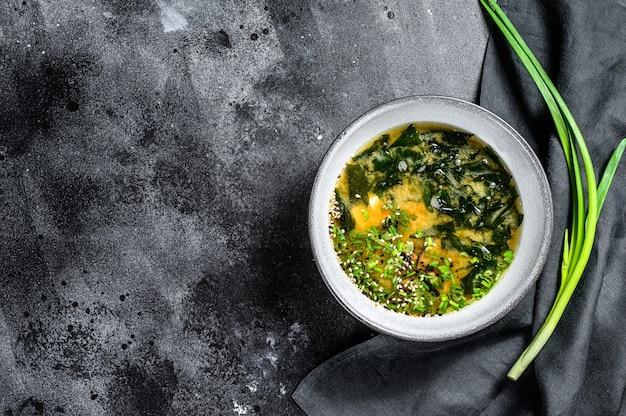 Sopa de missô com tofu e algas marinhas. fundo preto