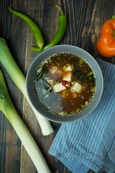 Sopa de missô com tofu e ervas. comida asiática. fundo escuro. espaço para texto.