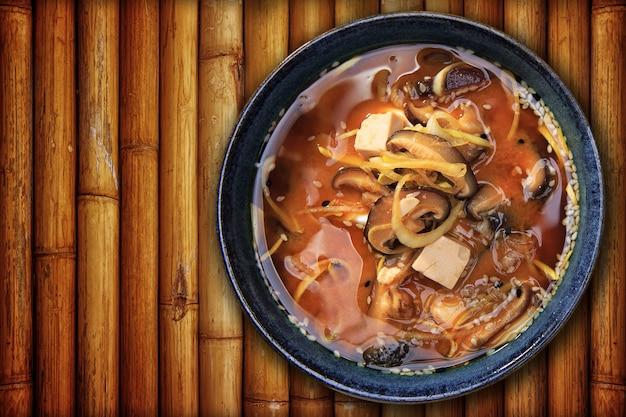 Sopa de missô em um prato de porcelana, em uma placa de bambu. vista do topo