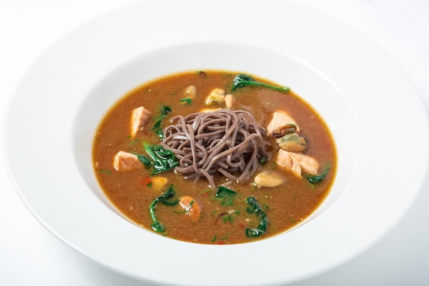 Sopa de missô saudável com macarrão de trigo sarraceno, peru e frutos do mar, decorado com verduras em prato branco