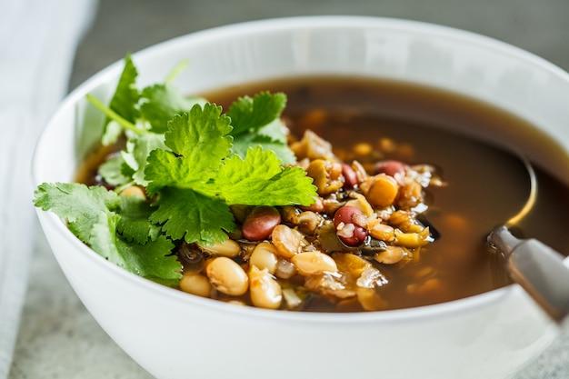 Sopa de mistura de feijão vegetariano em uma tigela branca. conceito de comida vegan.
