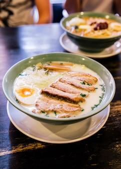 Sopa de osso de porco com creme de ramen (tonkotsu ramen) com carne de porco chashu, cebolinha, broto, cebola, menma e algas secas e ovo cozido.